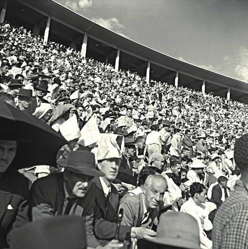 Torcedores acompanham jogo de futebol no Estádio do Pacaembu, na década de 50 de terno, gravata e chapéus feitos de jornal.